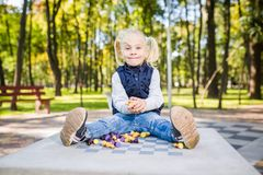 Funny Caucasian baby girl blonde does not want learn, does not want to school, want to play, laugh and indulge. child with hair. Ponytail sits table legs royalty free stock image