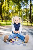 Funny Caucasian baby girl blonde does not want learn, does not want to school, want to play, laugh and indulge. child with hair. Ponytail sits table legs stock images