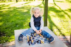 Funny Caucasian baby girl blonde does not want learn, does not want to school, want to play, laugh and indulge. child with hair. Ponytail sits table legs royalty free stock photography