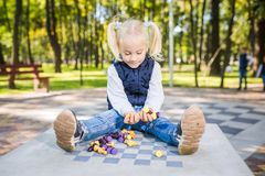 Funny Caucasian baby girl blonde does not want learn, does not want to school, want to play, laugh and indulge. child with hair. Ponytail sits table legs stock photos
