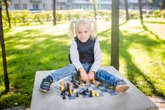 Funny Caucasian baby girl blonde does not want learn, does not want to school, want to play, laugh and indulge. child with hair. Ponytail sits table legs royalty free stock photo