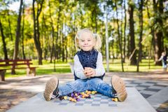 Funny Caucasian baby girl blonde does not want learn, does not want to school, want to play, laugh and indulge. child with hair. Ponytail sits table legs royalty free stock images