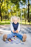 Funny Caucasian baby girl blonde does not want learn, does not want to school, want to play, laugh and indulge. child with hair. Ponytail sits table legs stock photo