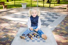 Funny Caucasian baby girl blonde does not want learn, does not want to school, want to play, laugh and indulge. child with hair. Ponytail sits table legs stock photography
