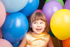 Funny Caucasian blond girl with colorful balloons Stock Photos