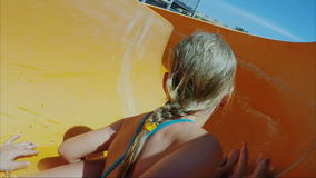 Funny Caucasian girl drives off the water slide with my mother. He laughs, looks at the camera, has fun and then falls stock footage