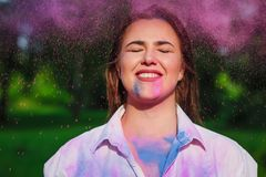 Funny caucasian model posing with closed eyes with exploding around pink Holi paint. Funny caucasian woman posing with closed eyes with exploding around pink stock images