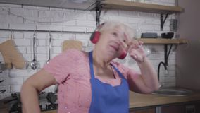 Funny caucasian old woman in headphones singing and dancing at the kitchen. Mature cheerful retiree enjoying life after stock footage