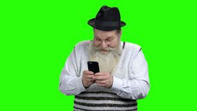 Funny caucasian pensioner using mobile phone. Old bearded man playing game on touch screen phone. Green Chroma Key background stock video footage