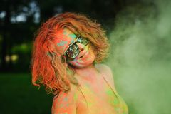 Funny caucasian model wearing glasses, posing in a cloud of green Holi paint. Funny caucasian woman wearing glasses, posing in a cloud of green Holi paint stock photography