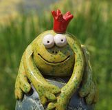 Funny ceramic frog prince with crown royalty free stock images
