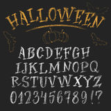 Funny chalk Halloween alphabet. Halloween chalk roman alphabet. White hand-drawn letters set on dark background. Funny decorations of bats and pumpkin Stock Image