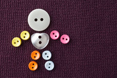 Funny character made of colorful sewing buttons with love heart shape central button. violet textured textile background Stock Photos