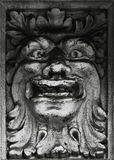 The funny character. Shot in black and white, detail on an sculpture representing an enigmatic character placed on the facade of this historic building, set in Stock Photos