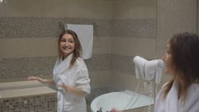 Funny charming girl in white robe took bath and sings in front of mirror with hairdryer.