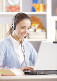 Funny chat. Female student chating on laptop with headset Royalty Free Stock Images