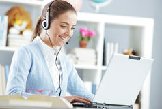 Funny chat. Young girl chating on laptop with headset Stock Image