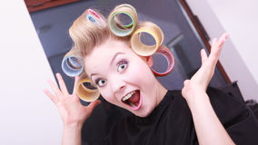 Funny cheerful blond girl hair curlers rollers by hairdresser in salon Royalty Free Stock Image