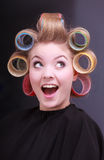 Funny cheerful blond girl hair curlers rollers by hairdresser in salon stock photo