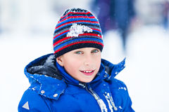 Funny cheerful boy in jacket and hat playing outdoors in winter Royalty Free Stock Photo