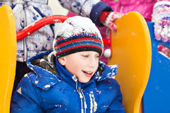Funny cheerful boy in jacket and hat sliding Royalty Free Stock Photography