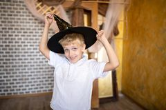 Cheerful boy wearing new wizard hat stock images