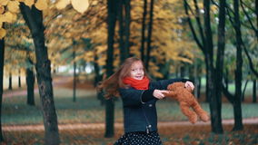 Funny, cheerful cute little girl spinning with her toy, teddy bear yellow leaves fall on them from the tree slow motion. Close-up funny, cheerful beautiful cute stock footage