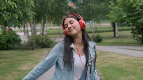 Funny cheerful girl dancing in the park listening to music on headphones. Fun mood. Funny cheerful happy girl in denim clothes dancing in the park during the day stock video footage