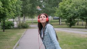 Funny Cheerful girl dancing in the park listening to music on headphones. Funny Cheerful girl in denim clothes dancing in the park listening to music in red stock video