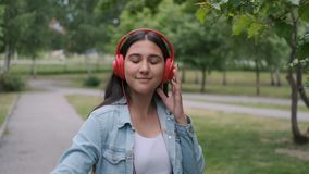 Funny cheerful girl dancing in the park near the trees listening to cheerful music in headphones. Fun mood. Portrait. Funny cheerful happy girl in jeans clothes stock video footage