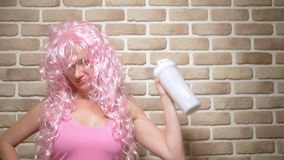 Funny cheerful girl with pink curly hair shakes a shaker against a brick wall background. Copy space stock video
