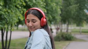 Funny cheerful girl dancing in the park listening to music on headphones. Fun mood. Close-up. Funny cheerful happy girl in denim clothes dancing in the park stock video