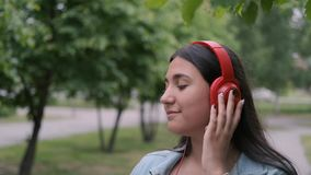 Funny cheerful girl dancing in the park near the trees listening to cheerful music in headphones. Fun mood. Close-up. Funny cheerful happy girl in jeans clothes stock video