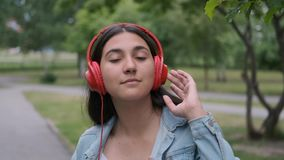 Funny cheerful girl dancing in the park near the trees listening to music on headphones. Fun mood. Close-up. Funny cheerful happy girl in jeans clothes dancing stock footage
