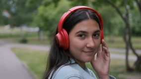 Funny cheerful girl dancing in the park near the trees listening to music on headphones. Fun mood. Portrait. Funny cheerful happy girl in jeans clothes dancing stock video footage