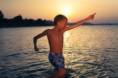 Funny cheerful little boy splashing water in sea at sunset jumping Royalty Free Stock Photography