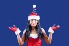 Funny cheerful Mrs. Claus. Looks to the camera with her hands up on blue background stock photography