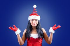 Funny cheerful Mrs. Claus looks to the camera. With her hands up on blue background stock photography