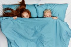 Funny cheerful smiling couple in love lying in the bed under blanket
