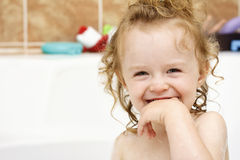 Funny cheerful toddler cleaning teeth in the bath Stock Image