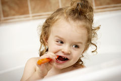 Funny cheerful toddler cleaning teeth in the bath Stock Photos