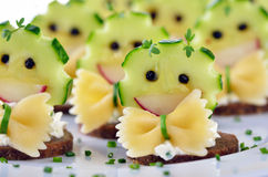 Funny cheese morsels. Funny morsels with spicy cream cheese, decorated with cucumber, radishes, pasta and pepper Royalty Free Stock Images