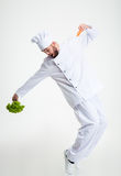 Funny chef cook dancing. Full length portrait of a funny chef cook holding vegetables and dancing isolated on a white background Royalty Free Stock Photo