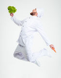 Funny chef cook dancing. Full length portrait of a funny chef cook dancing with vegetables isolated on a white background Royalty Free Stock Photos