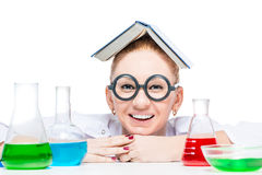 Funny chemist in round glasses with colorful flasks. On the table stock image