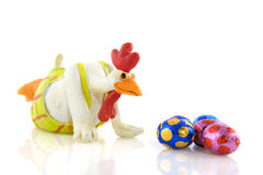 Funny chicken looks to easter eggs Stock Images