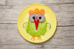 Funny chicken made of vegetables on plate and desk stock photo