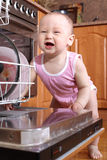 Funny child 1 year old in the kitchen at dishwasher Stock Images