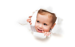 Funny  child baby girl peeping through hole in an empty white  p Royalty Free Stock Photos