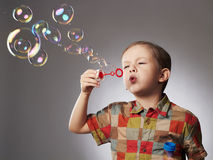 Funny child blowing soap bubbles. little boy Stock Photography